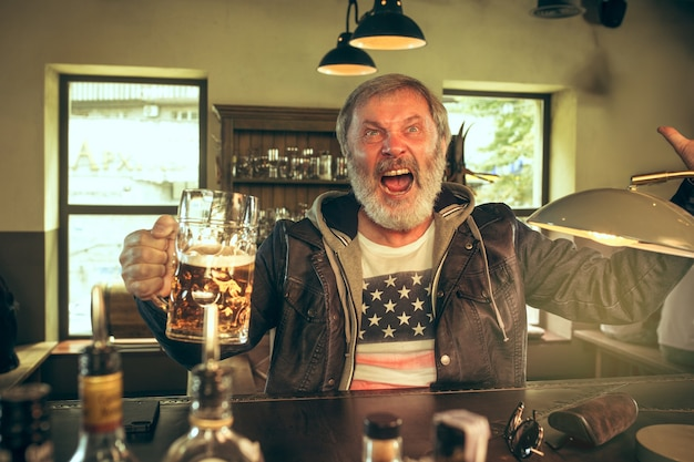 Hombre barbudo senior bebiendo alcohol en un pub y viendo un programa deportivo en la televisión. disfrutando de mi cerveza y mi cerveza favorita. hombre con jarra de cerveza sentado a la mesa. aficionado al fútbol o al deporte. concepto de emociones humanas