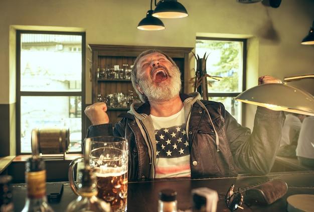 Hombre barbudo senior bebiendo alcohol en un pub y viendo un programa deportivo en la televisión.