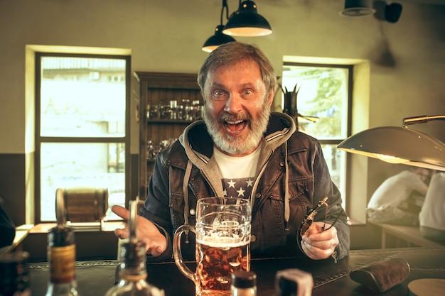 El hombre barbudo senior bebiendo cerveza en pub