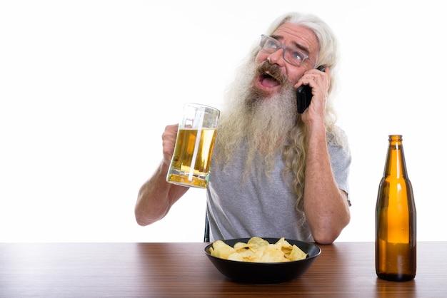 Hombre barbudo senior feliz pensativo sonriendo mientras habla por móvil