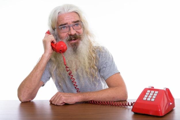Hombre barbudo senior feliz pensativo sonriendo mientras habla por teléfono antiguo