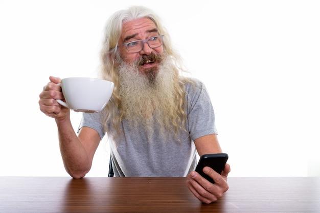 Hombre barbudo senior feliz pensativo sonriendo mientras sostiene el móvil