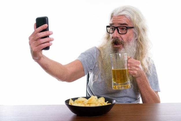 Hombre barbudo senior feliz sonriendo mientras toma foto selfie