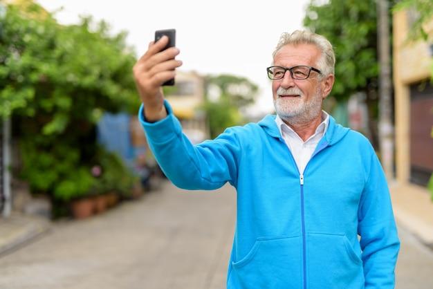 Hombre barbudo senior guapo feliz sonriendo mientras toma una foto selfie con teléfono móvil y usa anteojos al aire libre