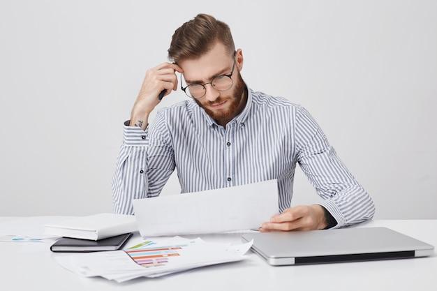 Hombre barbudo serio concentrado vestido formalmente, lee documento o contrato
