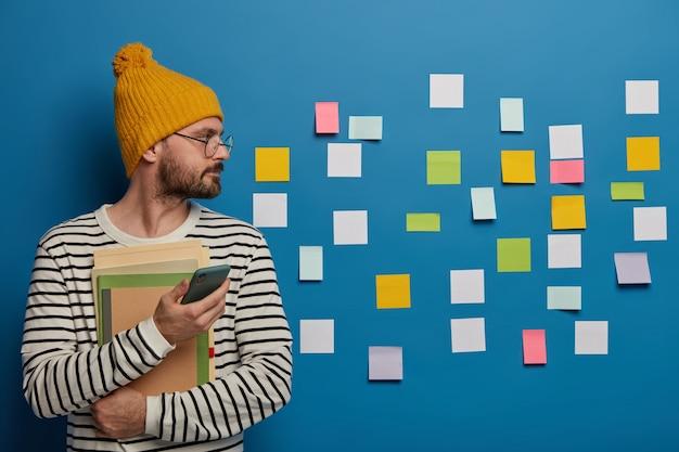 El hombre barbudo serio viste un sombrero amarillo y un jersey de rayas, se centró a un lado en la pared con notas adhesivas, utiliza un teléfono móvil