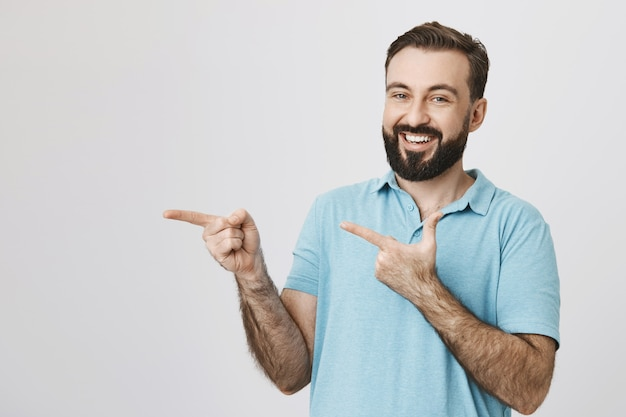 Hombre barbudo sonriente amable señalando con el dedo a la izquierda