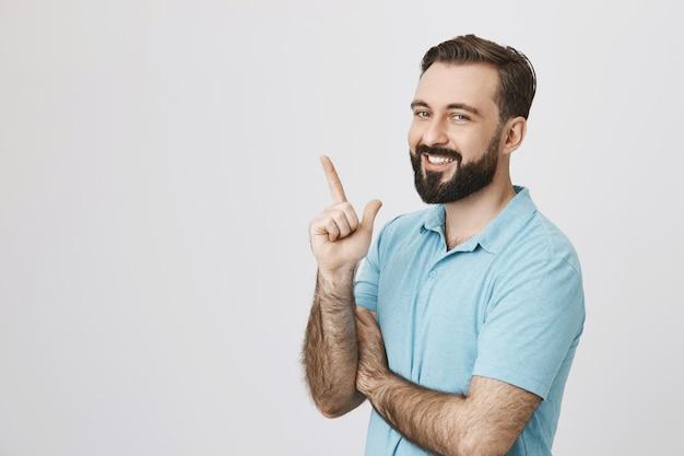 Hombre barbudo sonriente apuntando hacia la esquina superior izquierda