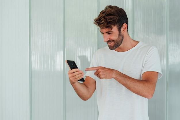 Hombre barbudo sonriente apuntando a teléfono celular