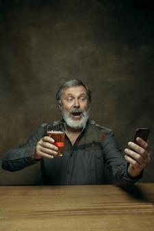 Hombre barbudo sonriente bebiendo cerveza en pub