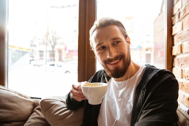 Hombre barbudo sonriente en café cerca de la ventana
