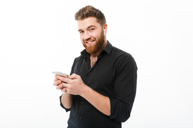 Hombre barbudo sonriente en camisa con smartphone