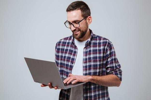 Hombre barbudo sonriente en eyeglases usando laptop
