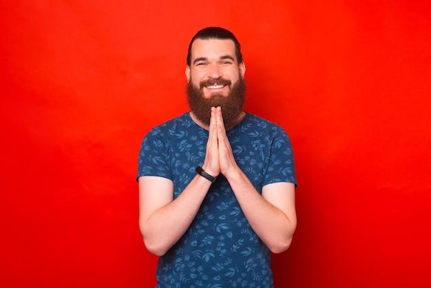 El hombre barbudo sonriente está juntando las manos como en una oración.