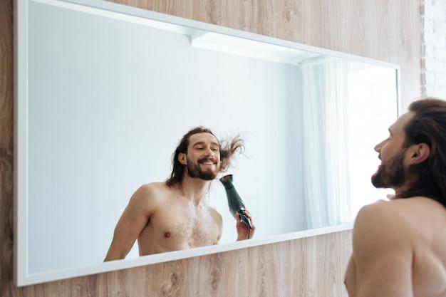 Hombre barbudo sonriente que seca el pelo con secador de pelo cerca del espejo