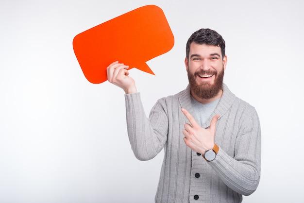 Hombre barbudo sonriente que señala en el bocadillo de diálogo rojo que se coloca sobre el fondo blanco