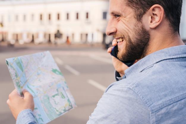 Hombre barbudo sonriente que sostiene el mapa mientras habla por teléfono celular