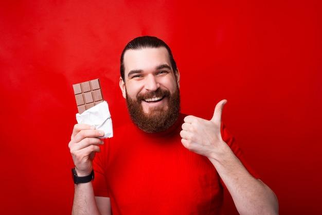 Hombre barbudo sonriente sosteniendo una barra de chocolate y mostrando el pulgar hacia arriba, buenos dulces