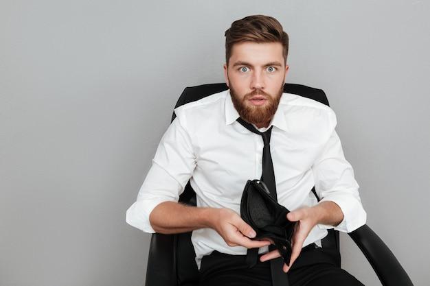 Hombre barbudo sorprendido en camisa blanca mostrando billetera vacía