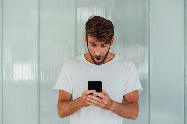 Hombre barbudo sorprendido con teléfono inteligente