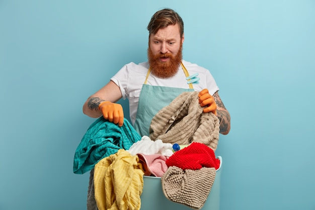 Hombre barbudo sostiene canasta de lavandería, abrumado por las tareas del hogar