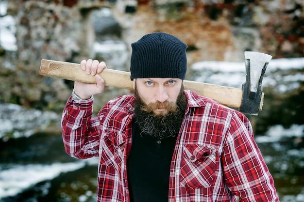 Hombre barbudo sostiene en sus manos un hacha en el bosque de invierno