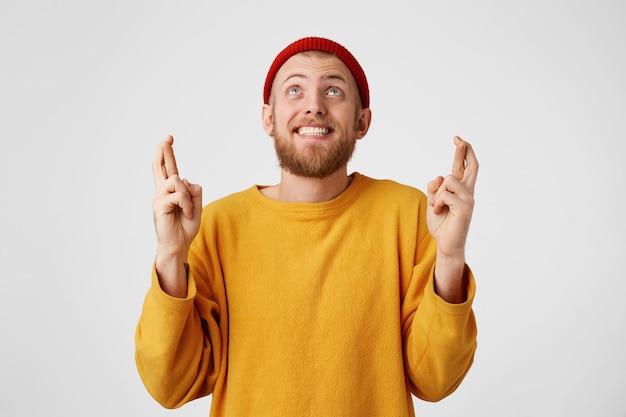 Hombre barbudo supersticioso cruza los dedos mirando hacia arriba deseando buena suerte