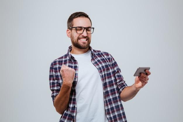 Hombre barbudo tan feliz en gafas con teléfono inteligente