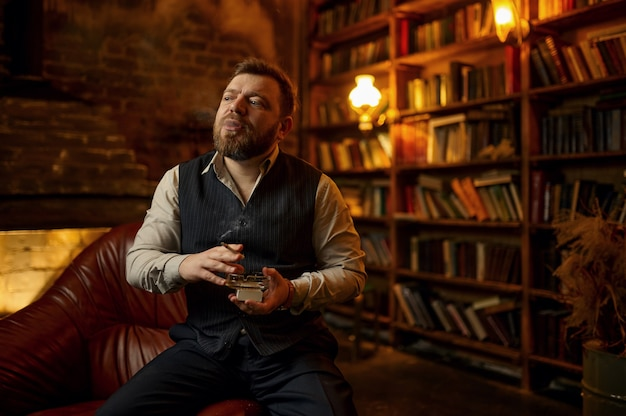 Hombre barbudo tiene cenicero y fuma cigarrillos, estantería y rico interior de oficina. cultura del tabaquismo, sabor específico