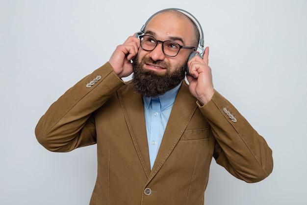 Hombre barbudo en traje marrón con gafas con auriculares mirando hacia arriba sonriendo disfrutando de su música favorita de pie sobre fondo blanco.