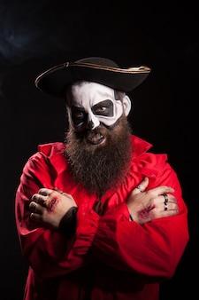 Hombre barbudo en traje de pirata con maquillaje espeluznante sobre fondo negro para halloween.
