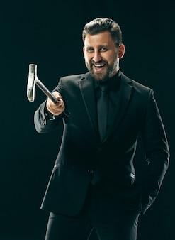 El hombre barbudo con traje sosteniendo bastón.