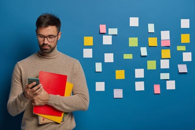 Hombre barbudo usa el teléfono móvil para conversar en línea, sostiene un libro de texto, usa anteojos, se viste con lentes y un suéter marrón, busca información, notas coloridas detrás de la pared