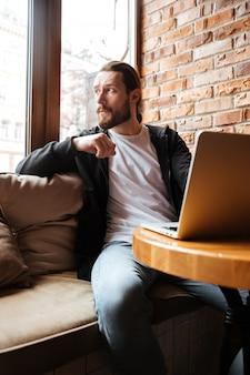 Hombre barbudo usando laptop en café y mirando a otro lado