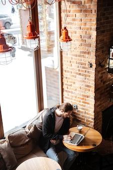 Hombre barbudo usando laptop en café
