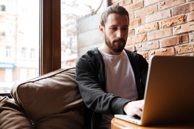 Hombre barbudo usando laptop cerca de la ventana en la cafetería