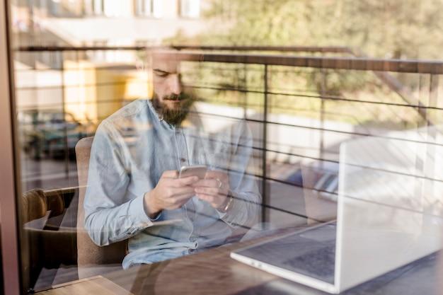 Hombre barbudo usando un teléfono móvil visto a través de un vidrio transparente en la cafetería.