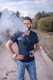 Hombre barbudo vape disfrutando de un dispositivo de humo electrónico en la calma al aire libre