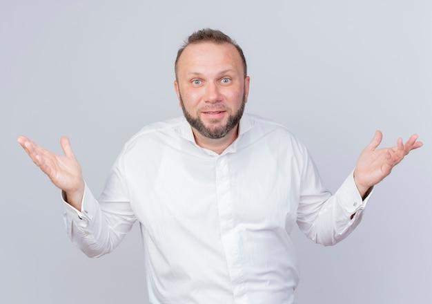 Hombre barbudo vestido con camisa blanca confundido extendiendo los brazos hacia un lado sin respuesta de pie sobre la pared blanca