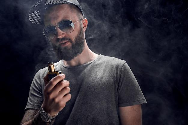 Hombre barbudo vestido con una camisa gris, gafas de sol y gorra de béisbol vaping