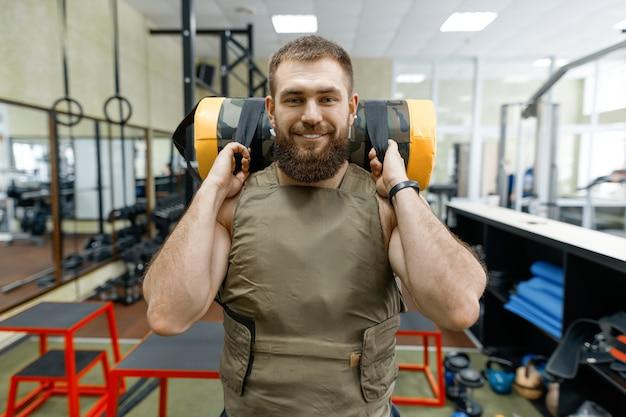 Hombre barbudo vestido con chaleco con pesas en el gimnasio, estilo militar