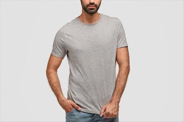 Hombre barbudo viste jeans y camiseta gret en blanco, está parado contra la pared de hormigón