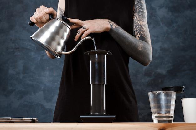 Hombre barista elaborando café. método alternativo aeropress.