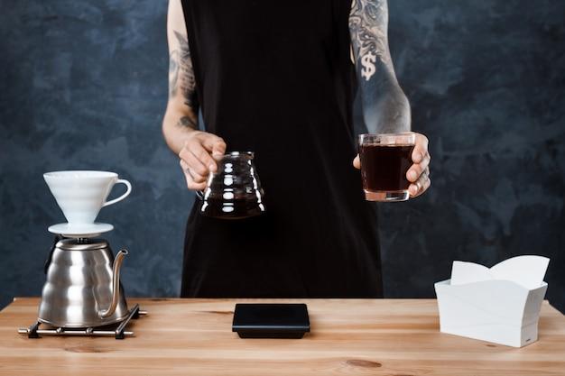 Hombre barista elaborando café. método alternativo verter más.