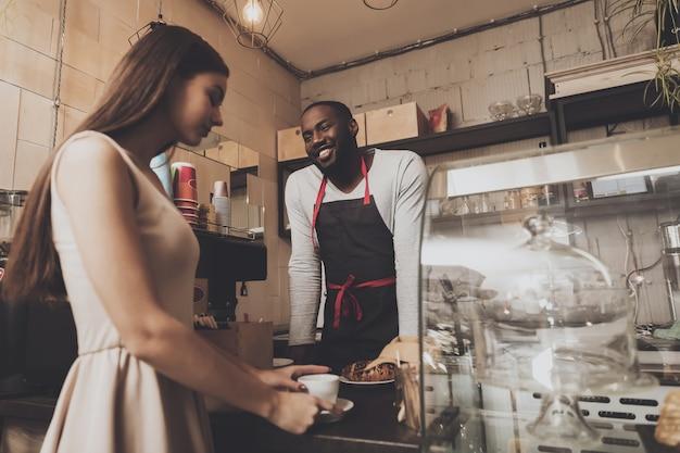 El hombre barista sonriente le da a una chica su orden