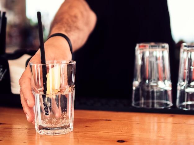 Hombre barman sirviendo vaso de bebida clara