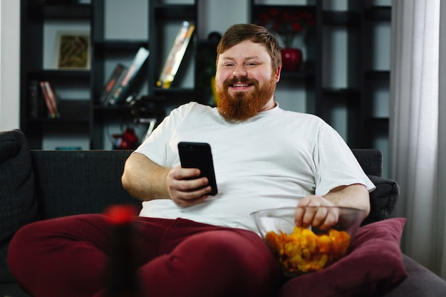 El hombre bastante gordo sonríe mirando su teléfono inteligente mientras que él se sienta en el sofá y come