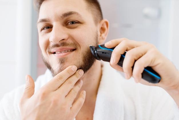Hombre en bata de baño se afeita la barba con una maquinilla de afeitar eléctrica en el baño.