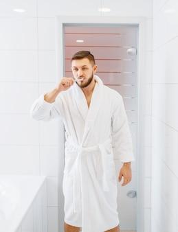 Hombre en bata de baño se cepilla los dientes en el baño.