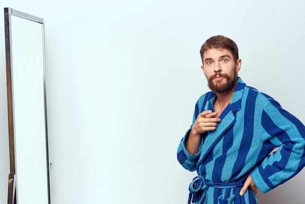 Un hombre en bata de baño en su casa, se mira en el espejo y habla reflejado.